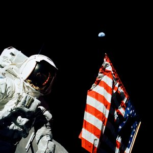 Scientist-astronaut Harrison H. Schmitt stands by the American flag during a moonwalk on the Apollo 17 mission. Home, that small dot in the blackness of space above the flag, is a quarter-million miles away.