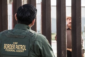 A US Border Patrol Officer talks to his counterpart on the other side of the fence. Photograph by Donovan.