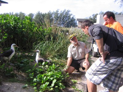 Greg Schubert shows Greg Baron and Noah Chesnin his garden of plants native to Sand Island