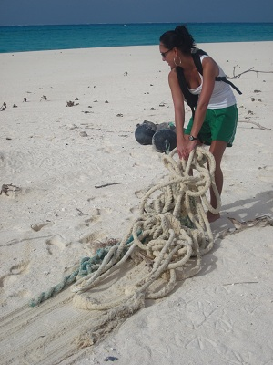 Hauling large heavy ropes from fishing vessels off the beach to reduce the possibilities of entanglement.