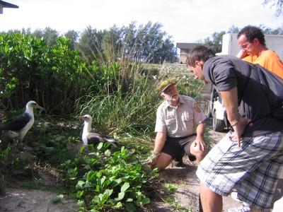 Greg Schubert shows Greg Baron and Noah Chesnin his garden of plants native to Sand Island