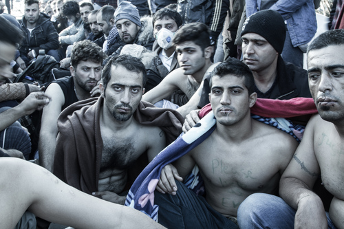 Refugees waiting to cross the blocked border from Greece to Macedonia. Some have sewn their lips shut in protest. Photo by Scott Carrier.