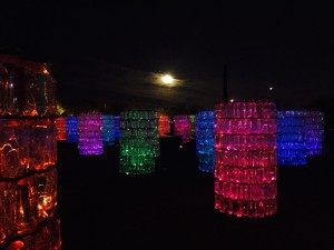 A beautiful art display involving plastic water bottles and light at the Desert Botanical Gardens in Phoenix, with the moon behind.
